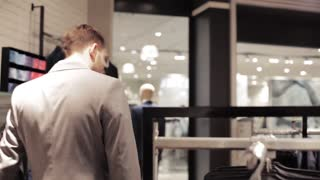 sale, shopping, fashion, style and people concept - elegant young man in suit choosing clothes in mall or clothing store or mall