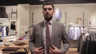 sale, shopping, fashion, style and people concept - happy young man trying suit at clothing store