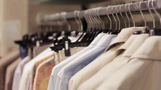 sale, shopping, fashion, style and people concept - man choosing clothes in mall or clothing store