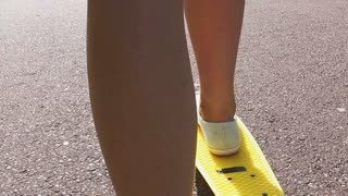 skateboarding, leisure, extreme sport and people concept - teenage girl feet riding short modern cruiser skateboard on road in slow motion mode