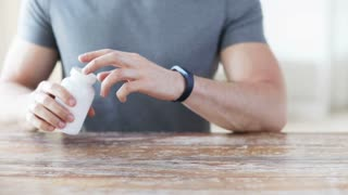 sport, healthy lifestyle, medicine, nutritional supplements and people concept - close up of man in fitness bracelet with glass of water pouring pills from jar to hand