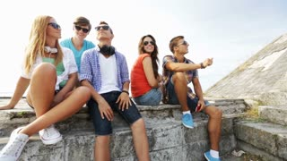 summer vacation, friendship, street life, technology and people concept - group of smiling teenagers hanging out and making selfie outdoors