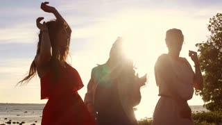 summer vacation, holidays, leisure, travel and people concept - group of happy smiling young women or teenage girls dancing on evening beach in slow motion mode
