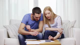 tax, finances, family, home and happiness concept - busy couple with papers and calculator at home