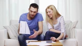 tax, finances, family, home and happiness concept - happy couple with papers and calculator at home