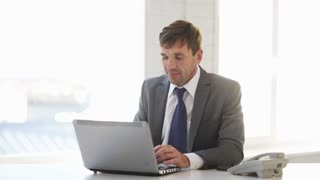technology, business and office concept - handsome businessman working with laptop computer taking a phone call