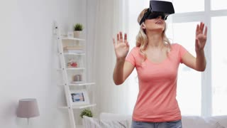 technology, cyberspace, entertainment, gaming and people concept - happy young woman with virtual reality headset or 3d glasses playing game at home