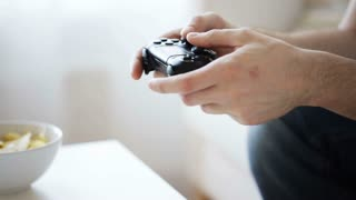 technology, lifestyle and people concept - close up of man hands with joystick and chips playing video game at home