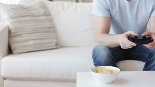 technology, lifestyle and people concept - close up of man with joystick and chips playing video game at home
