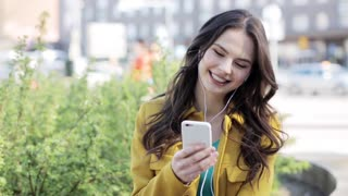 technology, lifestyle and people concept - smiling young woman or teenage girl with smartphone and headphones listening to music on city street