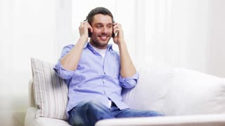 technology, music and happiness concept - smiling young man with headphones at home