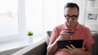 technology, online shopping, people and lifestyle concept - man with tablet pc computer and credit card sitting on sofa at home