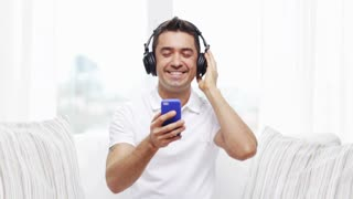 technology, people, lifestyle and distance learning concept - happy man with smartphone and headphones listening to music at home