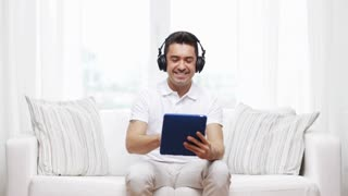technology, people, lifestyle and distance learning concept - happy man with tablet pc computer and headphones listening to music and shows thumbs up gesture at home