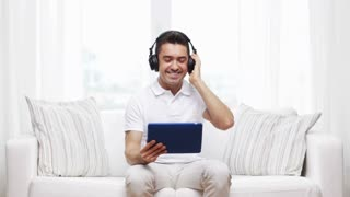 technology, people, lifestyle and distance learning concept - happy man with tablet pc computer and headphones listening to music at home