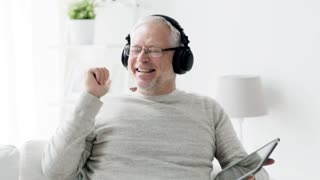 technology, people, lifestyle and distance learning concept - happy senior man with tablet pc computer and headphones listening to music and singing at home