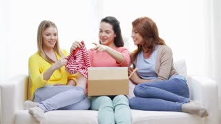 transportation, post and friendship concept - three smiling teenage girls opening cardboard box at home