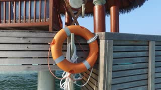 travel, tourism, safety, vacation and summer holidays concept - lifebuoy hanging on beach patio or terrace in sea water