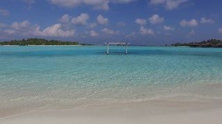 travel, tourism, vacation and summer holidays concept - blue sea lagoon with swing on maldives beach