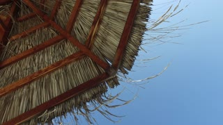 travel, tourism, vacation, beach and summer holidays concept - palapa or bungalow straw shed over blue sky
