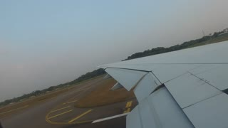 travel, transportation, aircraft, air transport and vehicle concept - wing of airplane landing on airport runway
