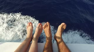 vacation, travel, cruise, people and leisure concept - bare feet on deck of sailboat or yacht sailing in sea