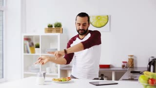 vegetarian food, healthy eating, people, technology and diet concept - man having sandwiches with coffee for breakfast and dancing to music playing on tablet pc computer at home kitchen