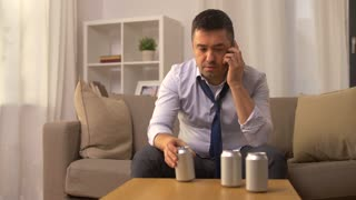 alcoholism, alcohol addiction and people concept - angry male alcoholic drinking canned beer or cocktail and calling on smartphone at home