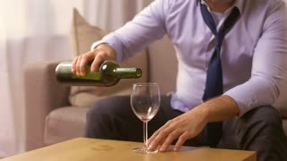 alcoholism, alcohol addiction and people concept - close up of male alcoholic pouring and drinking red wine to glass at home
