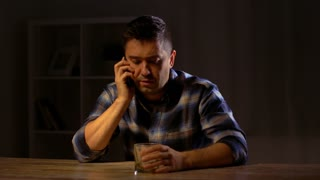 alcoholism, alcohol addiction and people concept - drunk male alcoholic drinking whiskey and calling on smartphone at night