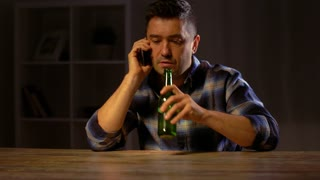 alcoholism, alcohol addiction and people concept - male alcoholic drinking beer from can and calling on smartphone at home