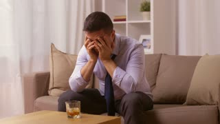 alcoholism, alcohol addiction and people concept - male alcoholic drinking whiskey at home