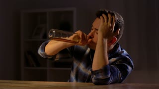 alcoholism, alcohol addiction and people concept - male alcoholic drinking whiskey from bottle at home