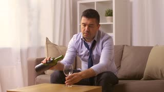 alcoholism, alcohol addiction and people concept - male alcoholic pouring and drinking red wine to glass at home