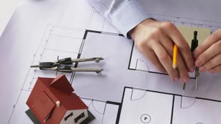 architecture, building and construction concept - male architect hands with compass measuring living house blueprint and taking notes