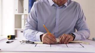 architecture, building and construction concept - male architect with ruler measuring living house blueprint and taking notes to notebook at office