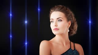beauty and glamour concept - seamless loop cinemagraph of gorgeous woman in evening dress and diamond earrings on black background with gleaming lights