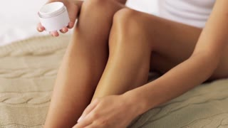 beauty and skin care concept - beautiful woman applying moisturizing cream to her legs at home bedroom