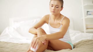 beauty and skin care concept - beautiful woman with epilator removing hair from legs sitting on bed at home bedroom