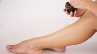 beauty, depilation, epilation, hair removal and people concept - beautiful woman with applicator applying depilatory wax to her leg