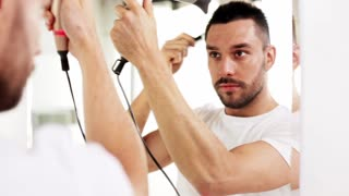 beauty, grooming and people concept - man with fan looking to mirror and drying his hair at home bathroom