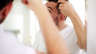 beauty, grooming and people concept - smiling young man looking to mirror and brushing hair with comb at home bathroom