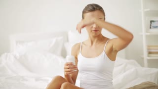 beauty, hygiene, bodycare and people concept - young woman applying antiperspirant or stick deodorant at home bedroom