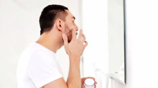 beauty, skin care and people concept - smiling young man applying cream to face and looking to mirror at home bathroom