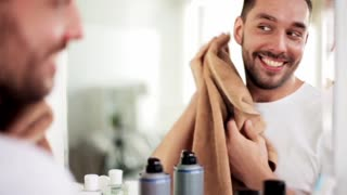 beauty, washing and people concept - man wiping his face with towel at bathroom