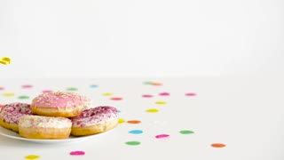 birthday party food concept - glazed donuts on plate and fruit juice or lemonade in decorated bottles with straws on table