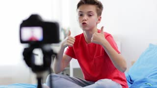 blogging, technology and people concept - happy smiling boy or blogger with camera recording video at home and showing thumbs up