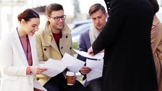 business and teamwork concept - international group of people with papers meeting outdoors