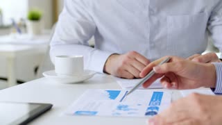 business, corporate and people concept - businessman and businesswomen with charts at office meeting