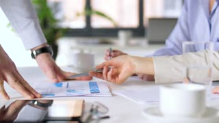 business, corporate and people concept - businessman showing papers with charts to businesswomen at office